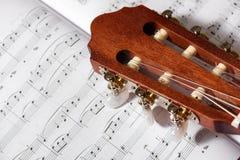 声学吉他特写镜头在音乐笔记的 免版税库存图片