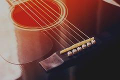 黑声学吉他,红蓝色被定调子的照片 免版税库存图片