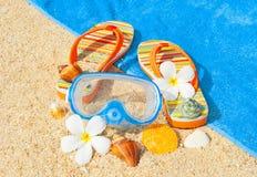 贝壳、潜水的在海滩的面具和sandalls 免版税库存照片
