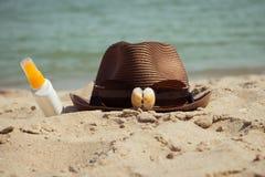 壳和太阳镜在帽子和一个瓶遮光剂化妆水 库存图片