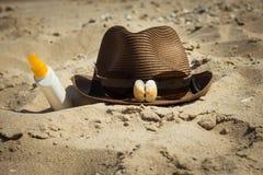 壳和太阳镜在帽子和一个瓶遮光剂化妆水 免版税库存照片