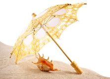 壳在沙子的一把伞下,白色背景 免版税库存图片