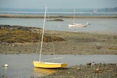 处于低潮中放置在多岩石的海滩的风船 免版税图库摄影