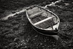 处于低潮中被停泊的小木划艇 库存图片
