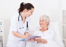 给处方的医生患者 免版税库存图片