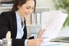 处理不同的文件的愉快的执行委员在办公室 免版税图库摄影