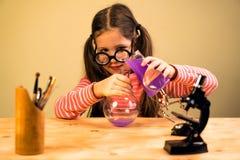 处理与化工烧瓶的小女孩化工家庭作业实验 儿童教育 免版税库存照片