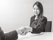 处理事务某人有愉快的面孔的在被弄脏的木书桌上的会议室和围住织地不很细的特写镜头亚洲妇女成功 免版税库存照片
