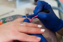 处理修指甲钉子桃红色涂层亮漆温泉沙龙 概念秀丽服务 美丽的女性手特写镜头 免版税图库摄影