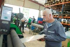 处理在机械上的资深工作者金属板板材 库存照片
