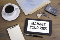处理您的风险 发短信在一张木桌上的片剂设备 库存图片