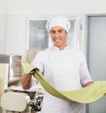 处理意粉面团板料的微笑的厨师 免版税库存照片