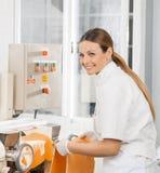 处理意粉面团板料的愉快的女性厨师 免版税库存图片