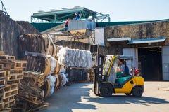 处理木板台的铲车操作员在仓库里 免版税库存照片