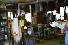 处理炽热玻璃的玻璃工厂劳工 库存图片