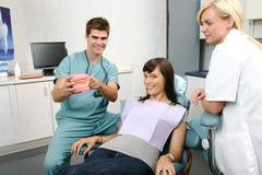 处理的牙科医生解释的患者 免版税库存照片