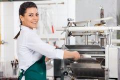 处理馄饨面团的愉快的女性厨师  库存照片