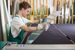 处理玻璃的片断玻璃剪裁工在车间 免版税库存图片