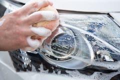 处理洗车概念-供以人员有的海绵的洗涤的汽车前灯 免版税库存图片