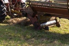 备草粮与一台老拖拉机的资深农夫 图库摄影
