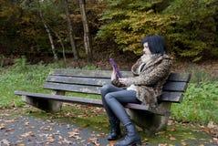 备选模型坐与片剂个人计算机的一条长凳 免版税库存照片