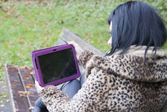 备选模型坐与片剂个人计算机的长凳 免版税库存图片