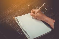 复制写下在有太阳光的白色笔记本的妇女手空间 免版税库存照片