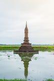 复制品寺庙,做由砖, Inkhothai一个池塘,剪影的中部有荷花的 免版税库存照片