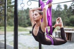 复制执行户外舒展妇女年轻人的空间 健身、舒展、平衡、锻炼和健康生活方式人民 使用吊床的妇女 图库摄影