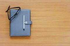 复制空间和软的焦点在固定式在与笔的木/顶视图和设计在日志书的构成和玻璃 免版税库存照片