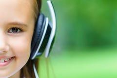 复制空间和年轻可爱的白种人与专业DJ耳机的女孩听的音乐的半面孔 库存图片
