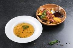 复杂晚餐 油煎的土豆用开胃烟肉和调味汁在一块木板材 图库摄影
