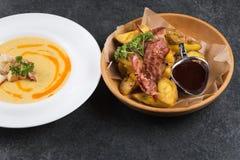 复杂晚餐 油煎的土豆用开胃烟肉和调味汁在一块木板材 免版税库存图片