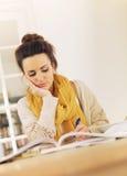 复核为她的检查的图书馆的大学生 免版税图库摄影