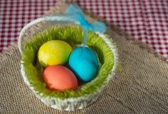 复活节上色了在一个篮子的鸡蛋在帆布餐巾和方格的桌布 库存图片