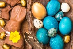 复活节上色了鸡蛋、巧克力兔宝宝和甜点在土气木背景 免版税图库摄影