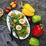 复活节与新鲜蔬菜的春天沙拉:蕃茄、芝麻菜、鸡蛋、坚果和油煎方型小面包片在灰色难看的东西背景 顶层 免版税图库摄影