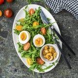 复活节与新鲜蔬菜的春天沙拉:蕃茄、芝麻菜、鸡蛋、坚果和油煎方型小面包片在灰色难看的东西背景 顶层 免版税库存照片