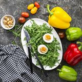 复活节与新鲜蔬菜的春天沙拉:蕃茄、芝麻菜、鸡蛋、坚果和油煎方型小面包片在灰色难看的东西背景 顶层 库存照片