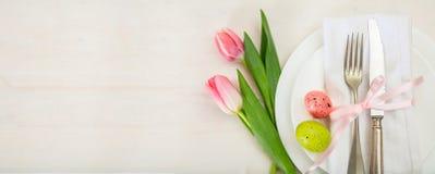 复活节与桃红色郁金香的桌设置在白色木背景 顶视图,拷贝空间,横幅 免版税图库摄影