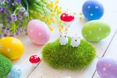 复活节与花的贺卡,复活节兔子兔宝宝在白色木板条戏弄并且怂恿 免版税库存照片