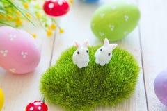 复活节与花的贺卡,复活节兔子兔宝宝在白色木板条戏弄并且怂恿 免版税图库摄影