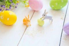 复活节与花的贺卡,复活节兔子兔宝宝在白色木板条戏弄并且怂恿 库存图片