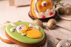 复活节与被绘的复活节兔子的绿色曲奇饼在白色切板和木表面的白色弓藏品草莓 免版税图库摄影
