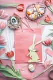复活节与郁金香、鸡蛋和装饰兔宝宝的问候布局在淡色的购物袋 免版税库存照片
