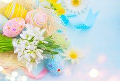 复活节五颜六色的蛋背景 与装饰的美丽的五颜六色的鸡蛋在蓝色木背景 免版税库存图片