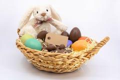 复活节修剪篮子用被绘的鸡蛋、朱古力蛋和鹌鹑蛋与复活节兔 库存照片