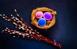 复活节假日、一个杨柳分支和装饰色的鸡蛋的装饰在具体蓝色背景的粗麻布,顶视图 免版税库存图片