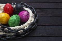 复活节假日概念用在绳索和链子的鸡蛋在木头 库存照片