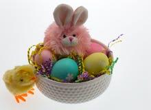 复活节兔子、小鸡和手被洗染的鸡蛋在白色碗有细片的 免版税库存图片